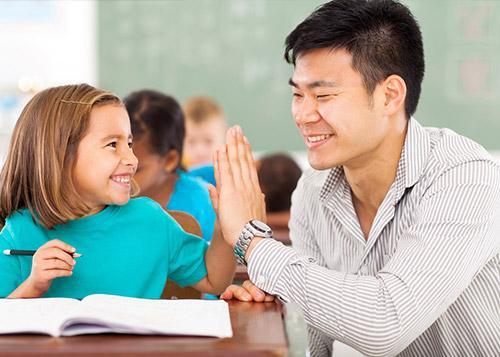 A school teacher gives a student a high-five.