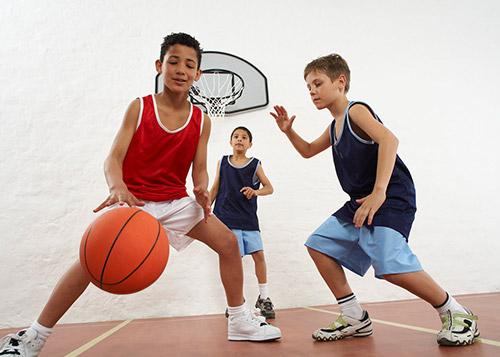 Three boys play basketball in an indoor basketball stadium.