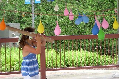 Girl swinging at hanging balloons with a bat