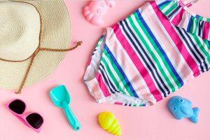 Beachwear and beach toys arranged on a wooden plank.