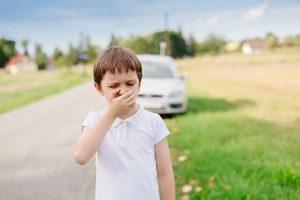 A boy feeling car sick after a long car drive.