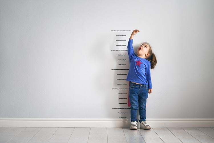 A little girl measuring her height.
