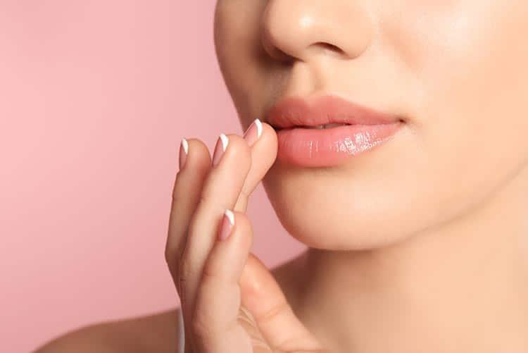 Woman applying lip balm to her lips