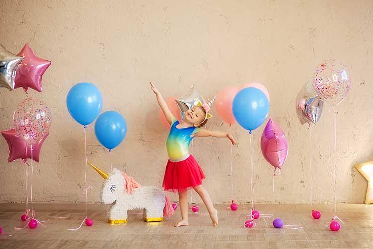 A girl dances around pretty balloons.