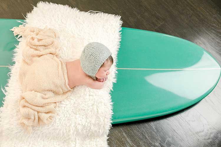 A newborn fast asleep on a surfboard.