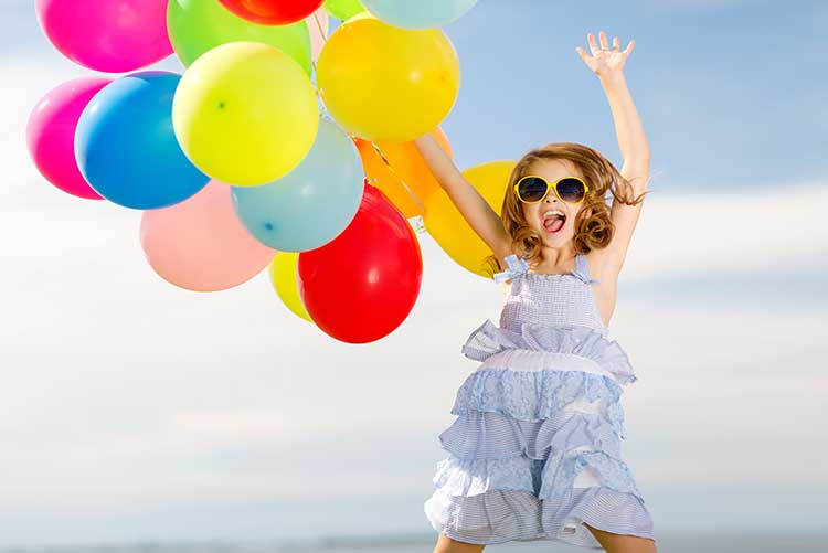 A girl dances while holding on to a bunch of balloons at a photoshoot.
