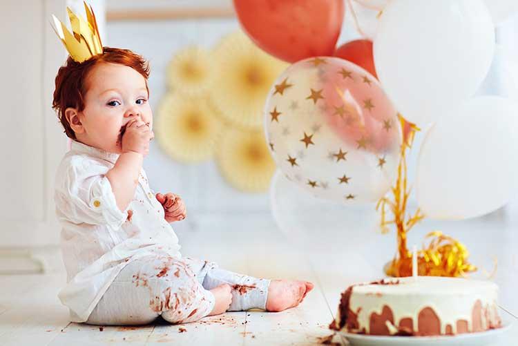 A baby boy munching on his birthday cake.